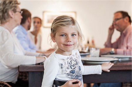 Portrait of girl sitting with family at dining table Stock Photo - Premium Royalty-Free, Code: 698-07587857