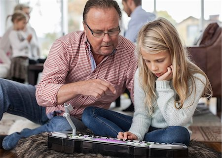 Grandfather and granddaughter playing piano with family in background at home Stock Photo - Premium Royalty-Free, Code: 698-07587869