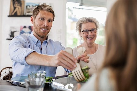 Smiling man serving salad to girl at home Stock Photo - Premium Royalty-Free, Code: 698-07587860