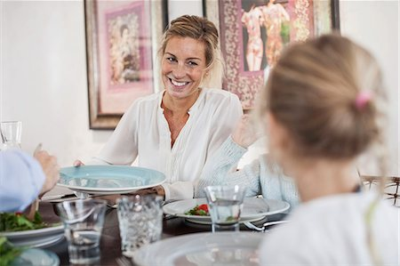 Smiling woman having lunch with family at dining table Stock Photo - Premium Royalty-Free, Code: 698-07587861