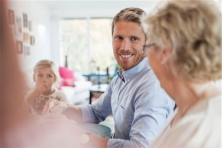 Smiling man looking at mother during lunch Stock Photo - Premium Royalty-Free, Code: 698-07587863