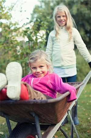 Portrait of playful sisters at yard Stock Photo - Premium Royalty-Free, Code: 698-07587878