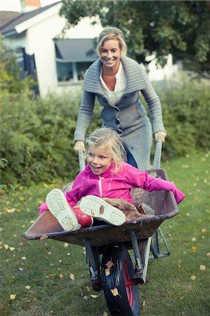 family  fun  outside - Playful mother pushing daughter on wheelbarrow at yard Stock Photo - Premium Royalty-Free, Code: 698-07587879