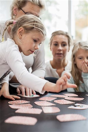 selecting - Girl playing card puzzle game with family at home Stock Photo - Premium Royalty-Free, Code: 698-07587871