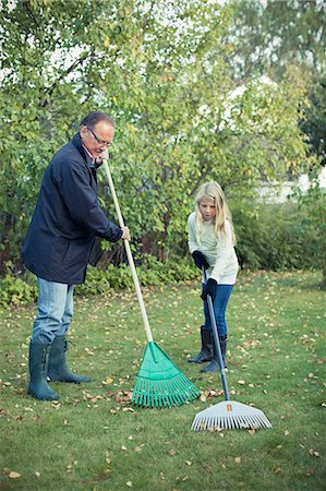 grandfather and granddaughter raking autumn leaves at yard Stock Photo - Premium Royalty-Free, Code: 698-07587880