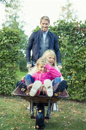 stockholm - Playful father pushing daughters on wheelbarrow at yard Stock Photo - Premium Royalty-Free, Code: 698-07587881