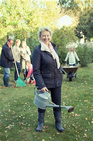 Portrait of senior woman carrying watering can while gardening with family at yard Stock Photo - Premium Royalty-Free, Code: 698-07587882