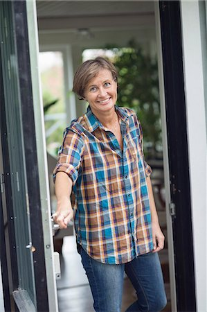 Portrait of mature woman opening door of house Stock Photo - Premium Royalty-Free, Code: 698-07587898