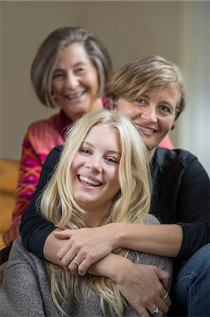 smiling - Portrait of three generation females sitting in a row at home Stock Photo - Premium Royalty-Free, Code: 698-07587891