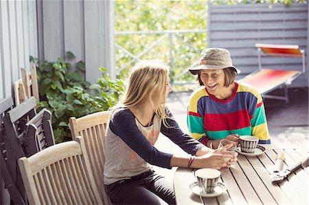 Grandmother and granddaughter having coffee in yard Stock Photo - Premium Royalty-Free, Code: 698-07587915