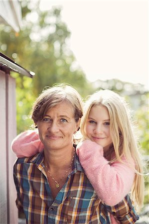 Portrait of smiling mother and daughter at yard Stock Photo - Premium Royalty-Free, Code: 698-07587912