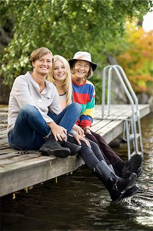 Portrait of three generation females sitting on pier Stock Photo - Premium Royalty-Free, Code: 698-07587920