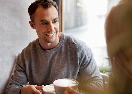 Young man having coffee with woman at cafe Stock Photo - Premium Royalty-Free, Code: 698-07587934