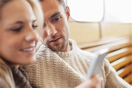 Couple using mobile phone together on ferry Stock Photo - Premium Royalty-Free, Code: 698-07587948
