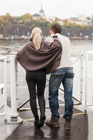 Rear view of young couple leaning on railing outdoors Stock Photo - Premium Royalty-Free, Code: 698-07587949
