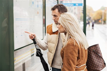 stock photograph - Young couple reading time table on bus stop Stock Photo - Premium Royalty-Free, Code: 698-07587969