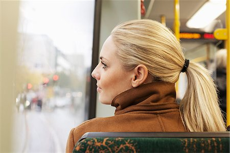 Rear view of woman looking out through bus window Stock Photo - Premium Royalty-Free, Code: 698-07587974