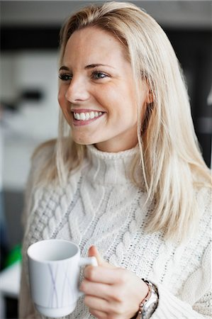 Smiling businesswoman holding coffee mug in office Stock Photo - Premium Royalty-Free, Code: 698-07587979