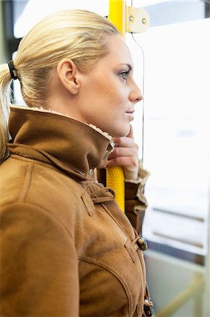 Side view of woman holding railing on bus Stock Photo - Premium Royalty-Free, Code: 698-07587971