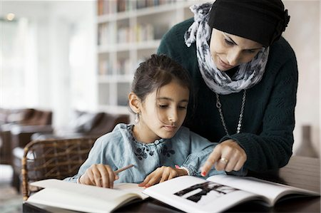 Mother assisting girl in doing homework at table Stock Photo - Premium Royalty-Free, Code: 698-07588000