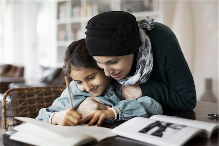 Mother embracing daughter studying at home Stock Photo - Premium Royalty-Free, Code: 698-07588001