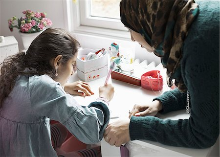 Mother helping girl in doing homework at desk Stock Photo - Premium Royalty-Free, Code: 698-07588014