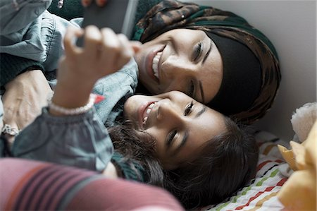 focus on background - Playful mother and daughter using mobile phone in bedroom Stock Photo - Premium Royalty-Free, Code: 698-07588020