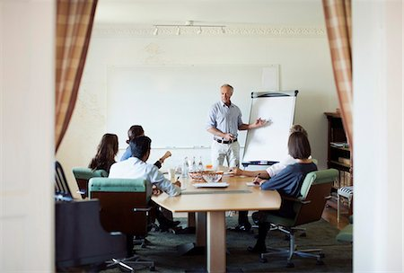 Senior businessman giving presentation in board room Stock Photo - Premium Royalty-Free, Code: 698-07588031