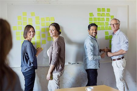 self adhesive note - Happy business people standing by whiteboard at office Stock Photo - Premium Royalty-Free, Code: 698-07588044
