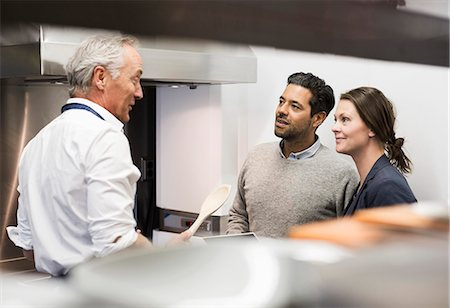 Chef talking to business people in commercial kitchen Stock Photo - Premium Royalty-Free, Code: 698-07588059