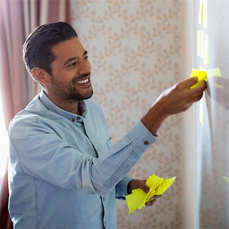 self adhesive note - Smiling businessman removing memo notes from whiteboard in office Stock Photo - Premium Royalty-Free, Code: 698-07588052