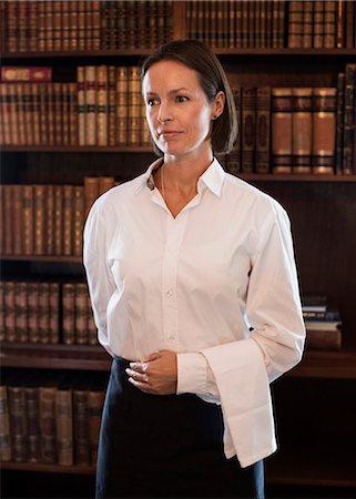 Confident waitress standing against bookshelf in restaurant Stock Photo - Premium Royalty-Free, Code: 698-07588069