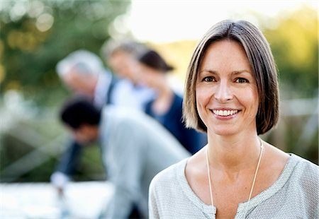 Portrait of happy businesswoman at patio with colleagues in background Stock Photo - Premium Royalty-Free, Code: 698-07588076