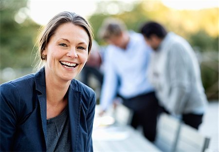 Portrait of businesswoman laughing at patio with colleagues in background Stock Photo - Premium Royalty-Free, Code: 698-07588079