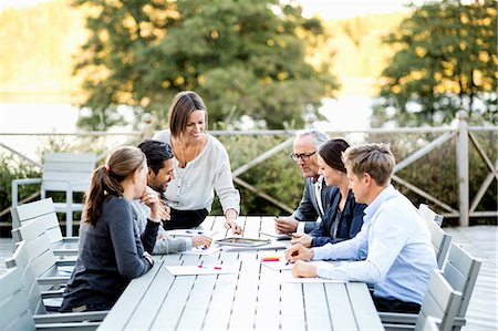 event - Group of business people working at table on patio Stock Photo - Premium Royalty-Free, Code: 698-07588082