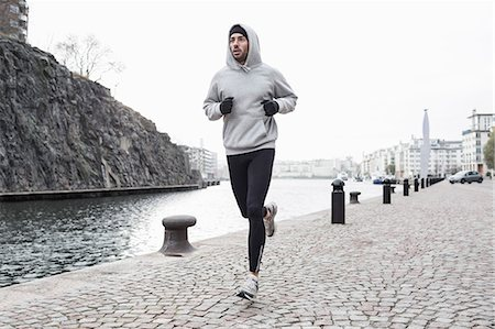 Man jogging at canal side Stock Photo - Premium Royalty-Free, Code: 698-07588099