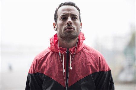 Sporty man in jacket listening to music through headphones Stock Photo - Premium Royalty-Free, Code: 698-07588104
