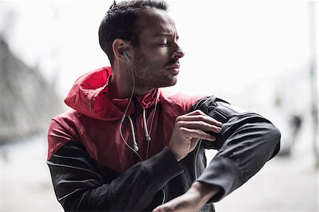 Sporty man adjusting arm band while listening to music Stock Photo - Premium Royalty-Free, Code: 698-07588105