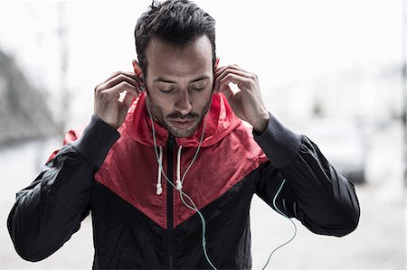 Sporty man in jacket adjusting headphones Stock Photo - Premium Royalty-Free, Code: 698-07588106