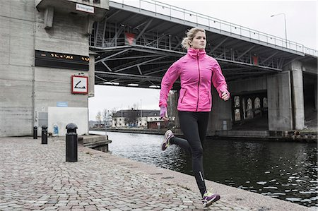 physical fitness - Full length of woman jogging against bridge Stock Photo - Premium Royalty-Free, Code: 698-07588100