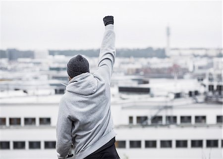 Sporty man celebrating success against buildings Stock Photo - Premium Royalty-Free, Code: 698-07588118