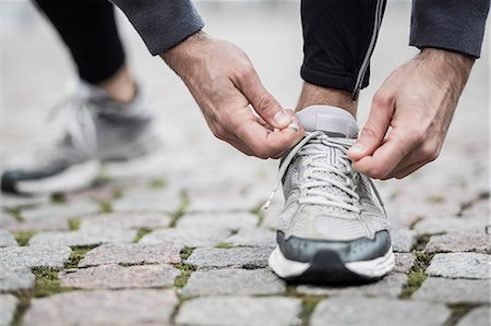 Low section of man tying lace of sports shoe Stock Photo - Premium Royalty-Free, Code: 698-07588113