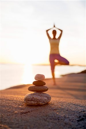 Pile of stones with woman practicing yoga in background at lakeshore Stock Photo - Premium Royalty-Free, Code: 698-07588127