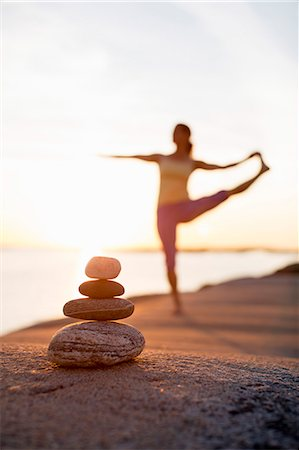 Woman practices yoga on lakeshore with focus on pile of stones Stock Photo - Premium Royalty-Free, Code: 698-07588128