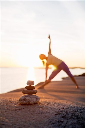 Woman practices yoga on lakeshore with focus on stack of stones Stock Photo - Premium Royalty-Free, Code: 698-07588129