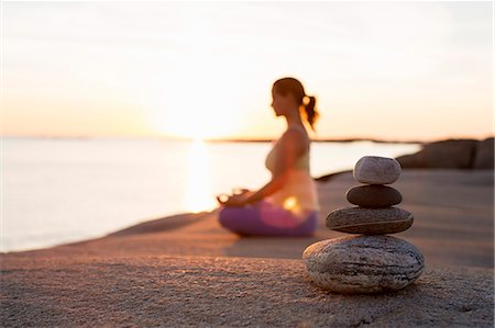 Side view of woman sitting in lotus position on lakeshore with focus on stack of stones Stock Photo - Premium Royalty-Free, Code: 698-07588131