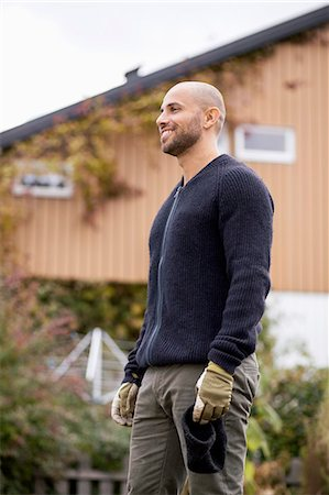 Smiling man standing at yard during winter Stock Photo - Premium Royalty-Free, Code: 698-07588140