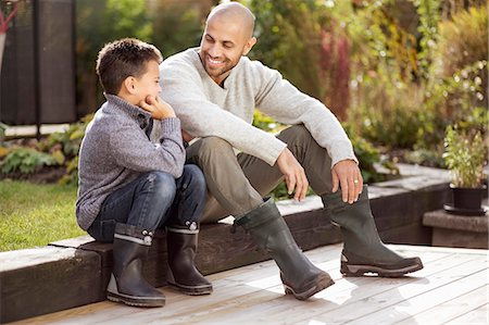 rear - Father and son sitting at yard Stock Photo - Premium Royalty-Free, Code: 698-07588157