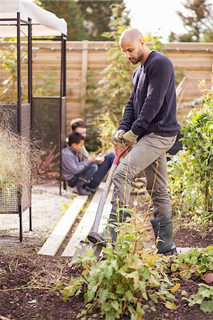 Man digging in garden with children in background Stock Photo - Premium Royalty-Free, Code: 698-07588151