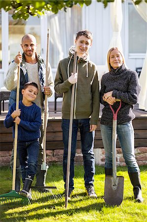 season - Portrait of confident family with gardening equipment standing at yard Stock Photo - Premium Royalty-Free, Code: 698-07588169